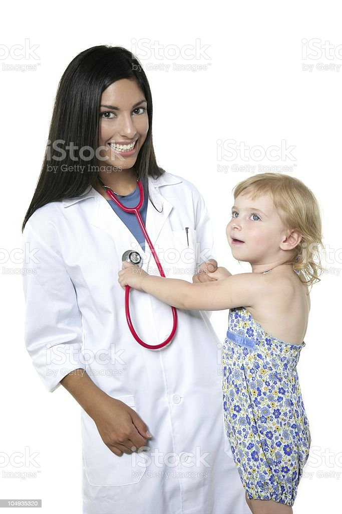 Brunette pediatric doctor with blond little girl royalty-free stock photo