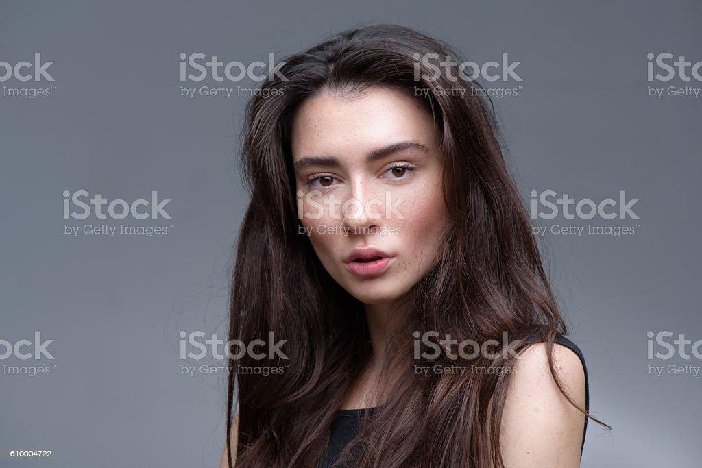 brunette posing in the studio, isolated on light grey background stock photo