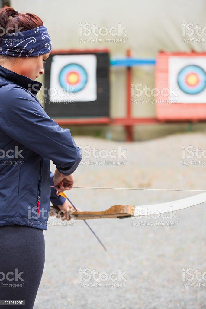 Brunette preparing her bow and arrow stock photo
