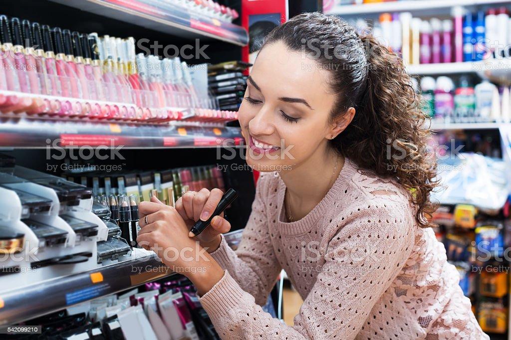 Brunette shopping in beauty store stock photo