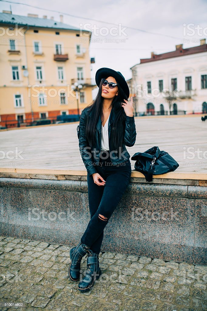 Brunette  sitting on a bench in the city streets. stock photo
