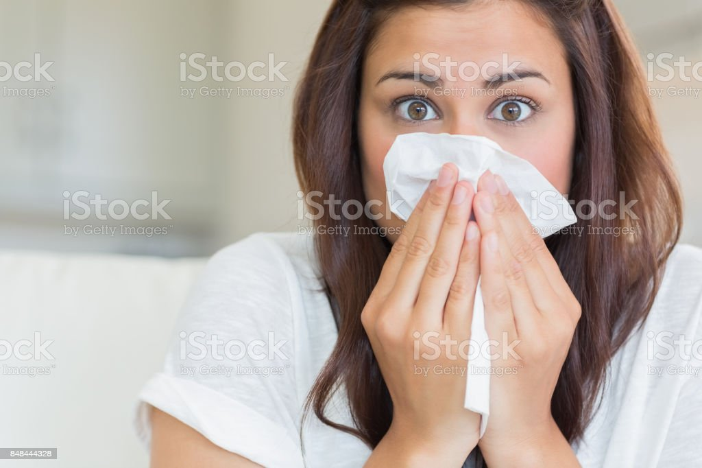 Brunette sneezing and looking surprised stock photo