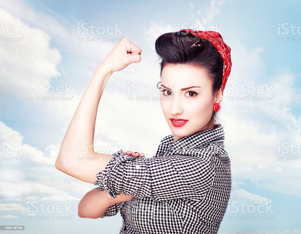 Brunette striking a famous Rosie Riveter pose stock photo