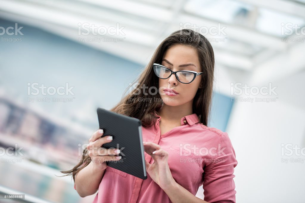 Brunette with eyeglasses and tablet stock photo