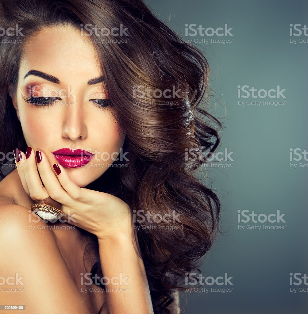 Brunette with long curled hair. Luxury fashion style. stock photo