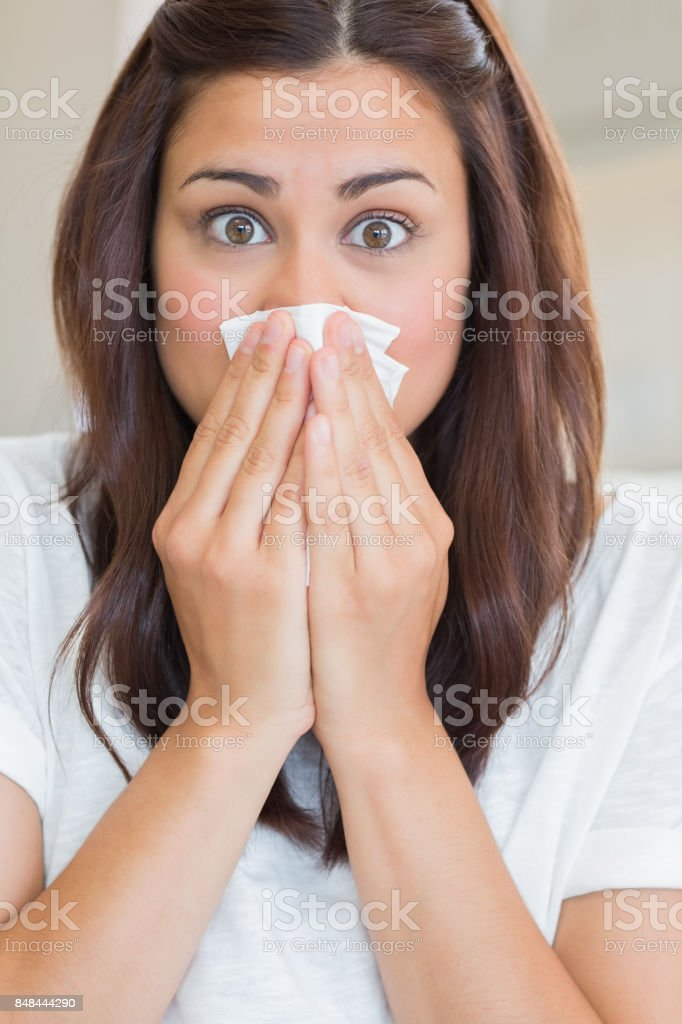 Brunette with runny nose looking surprised stock photo
