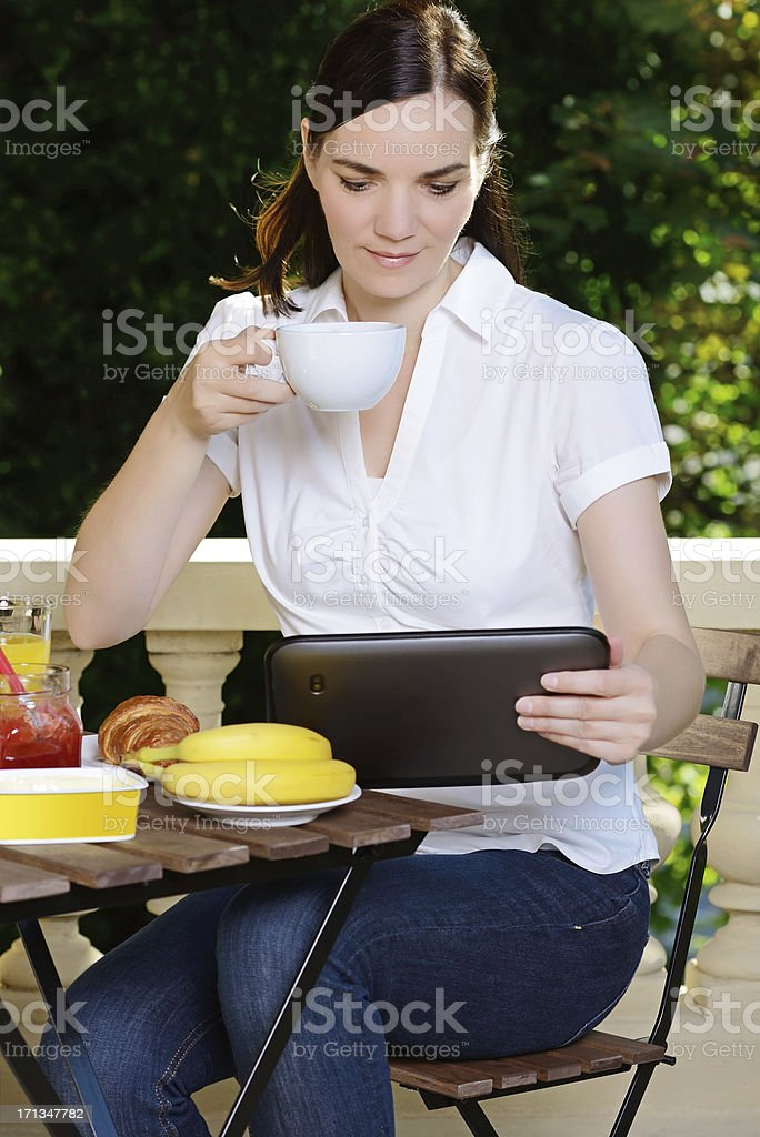 Brunette Woman at Breakfast with Tablet PC Summer stock photo