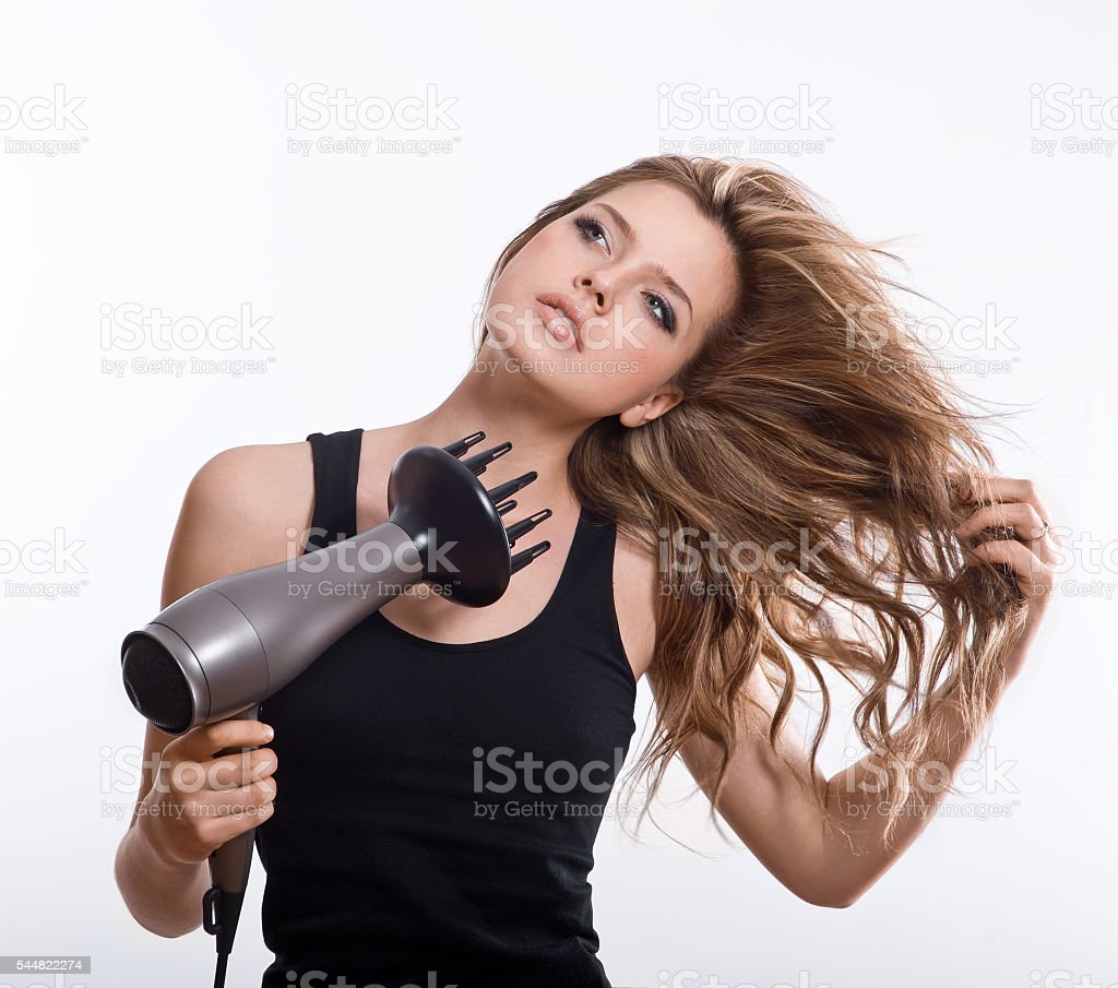 Brunette woman blow-drying long hair stock photo