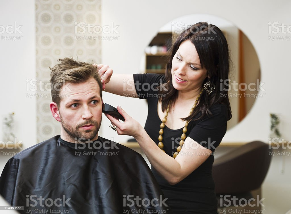 Brunette woman clipping a man's hair in a salon stock photo