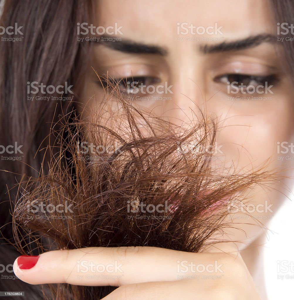 Brunette woman frowning at split ends stock photo