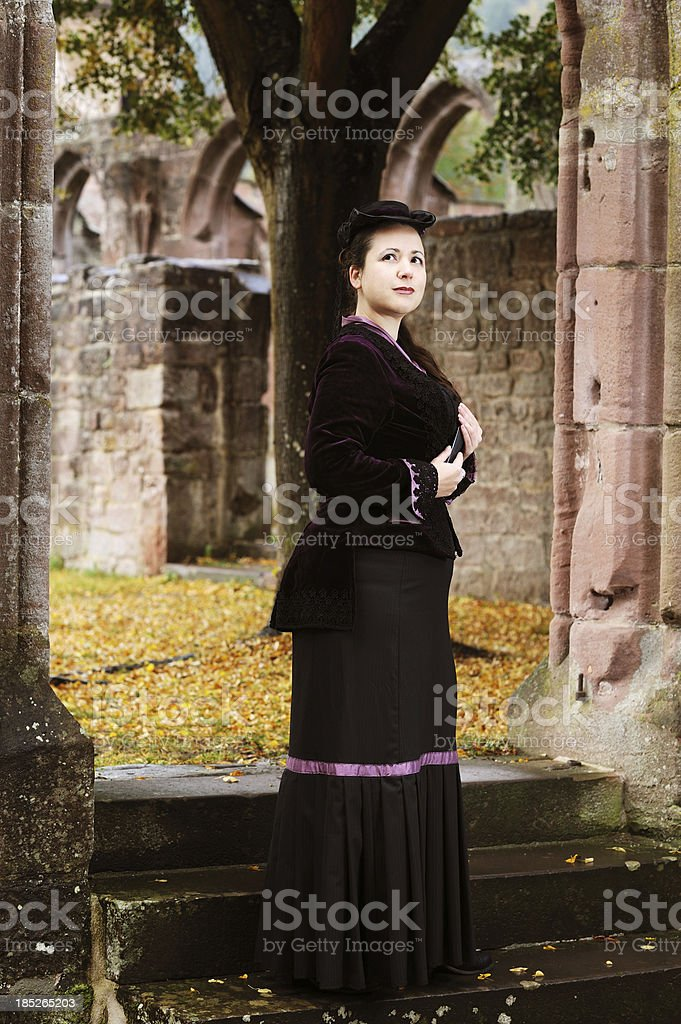 Brunette Woman Historical Dress between Ruins Fall Time stock photo