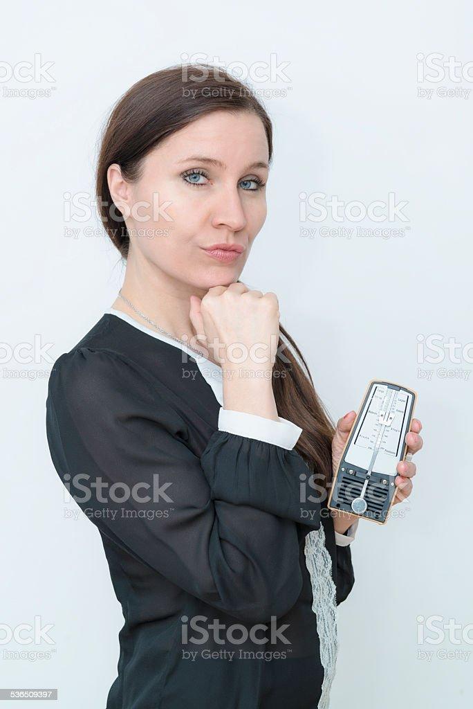 Brunette woman holding a metronome stock photo