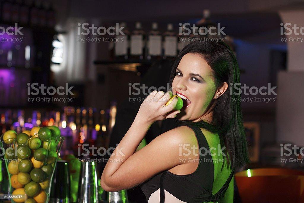Brunette woman in bar bite fruit royalty-free stock photo