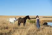 Brunette woman in field with horses