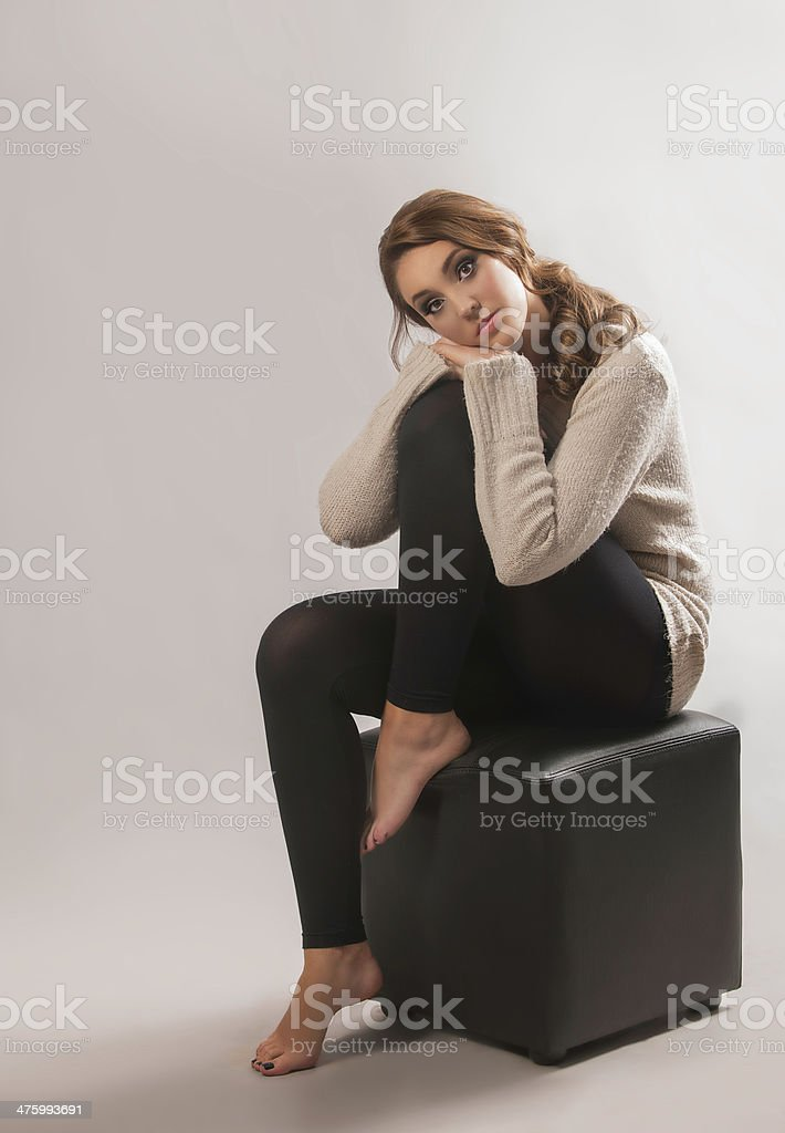 Brunette woman in jersey and tights leaning on her leg stock photo