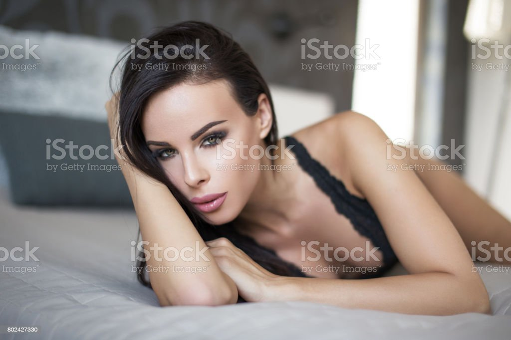 Brunette woman in underwear lying on bed stock photo