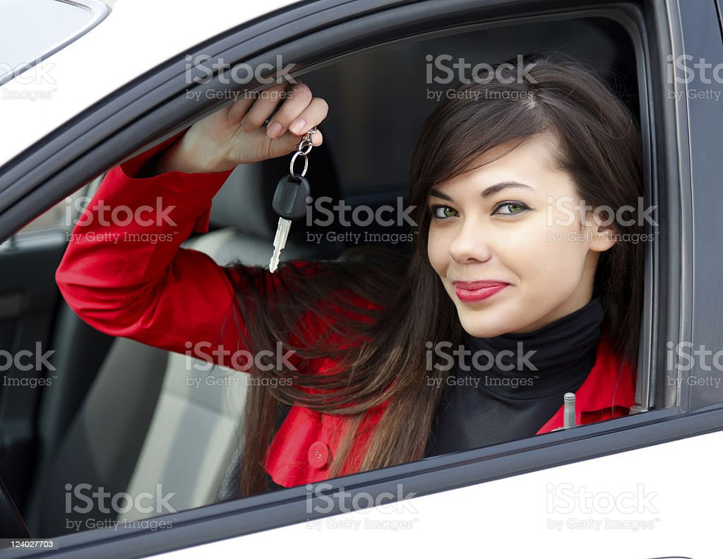 Brunette woman in white car wearing a red coat with car keys royalty-free stock photo