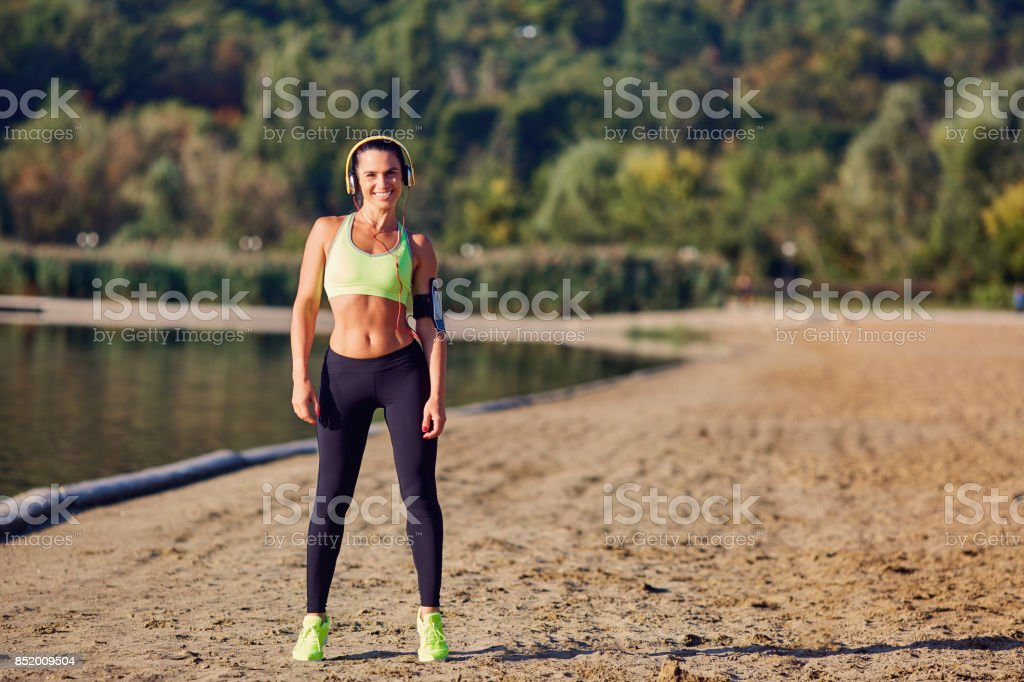 A brunette woman is an athlete runner in the park before jogging stock photo