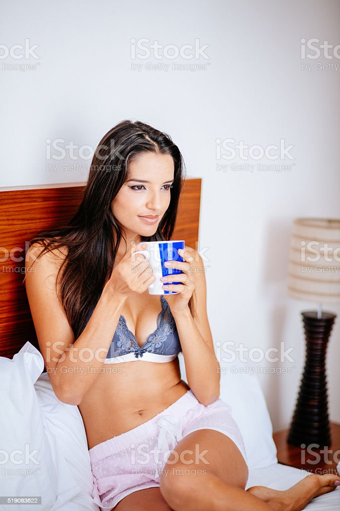 Brunette Woman is drinking a cup of coffee in morning stock photo