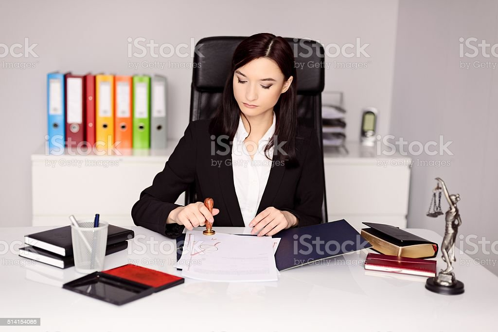 Brunette woman Notary Public notarizes notary act stock photo
