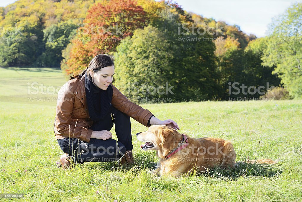Brunette Woman Playing with Dog Outdoors in Autumn royalty-free stock photo