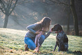 Brunette woman posing with her adorable German pointer dog outdoor