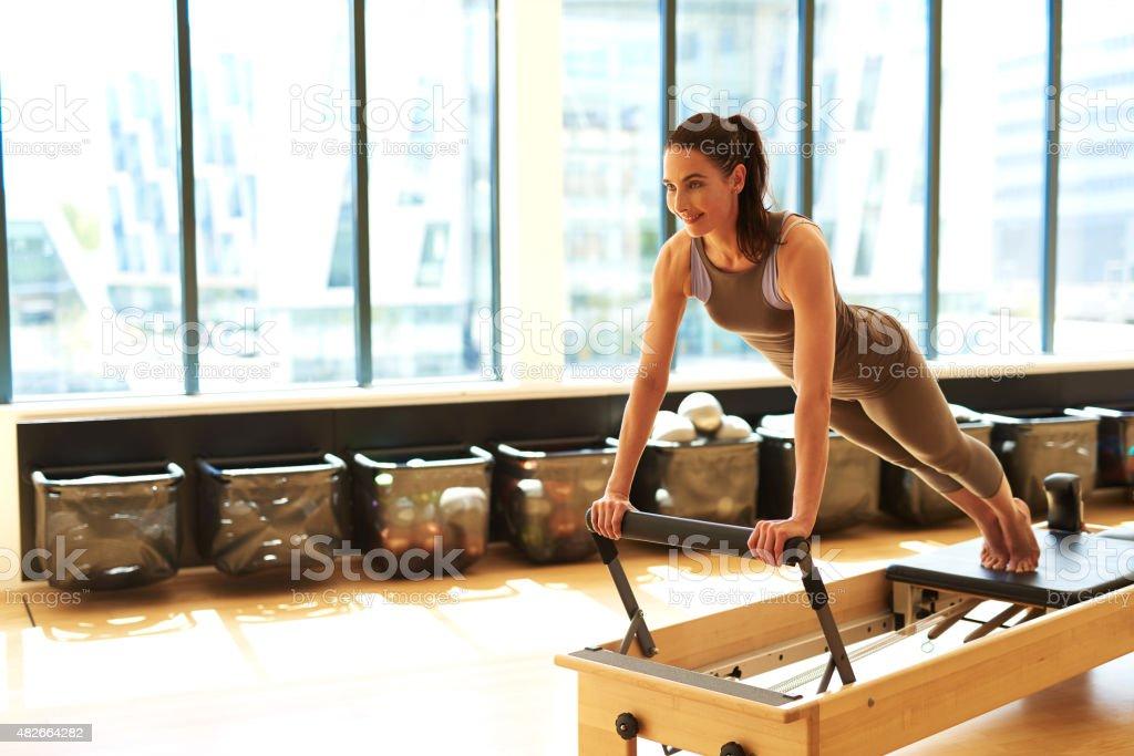 Brunette Woman Practicing Pilates in Studio stock photo