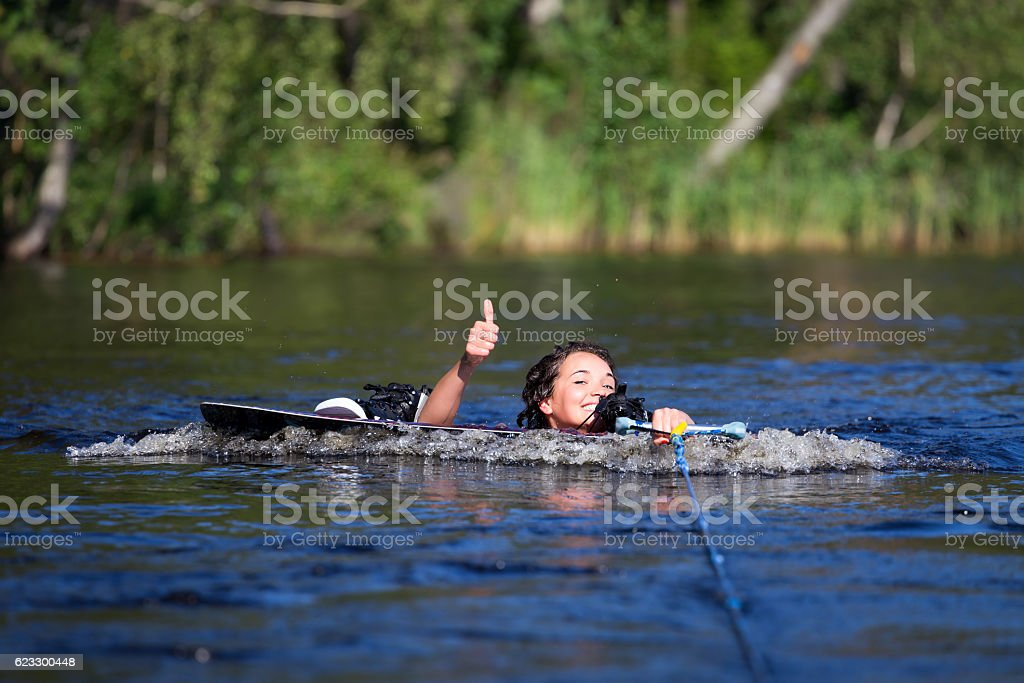 brunette woman riding wakeboard in a summer lake stock photo