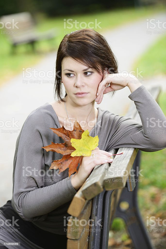 Brunette Woman sitting on a park bench thinking royalty-free stock photo