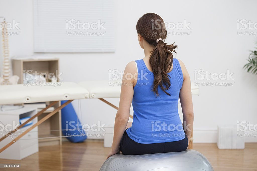 Brunette woman sitting on a therapy ball stock photo