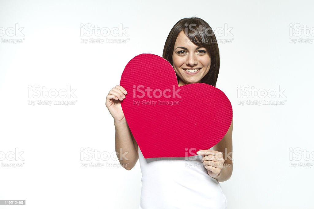 A brunette woman smiling and holding a red heart cutout royalty-free stock photo