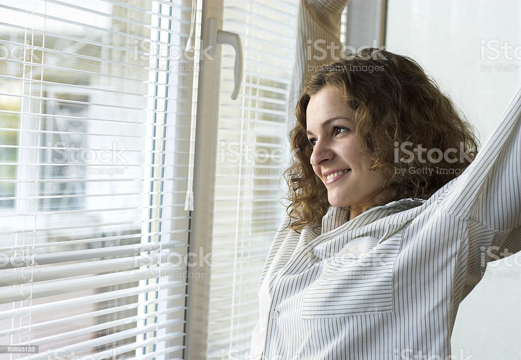A brunette woman smiling out the window after getting up royalty-free stock photo