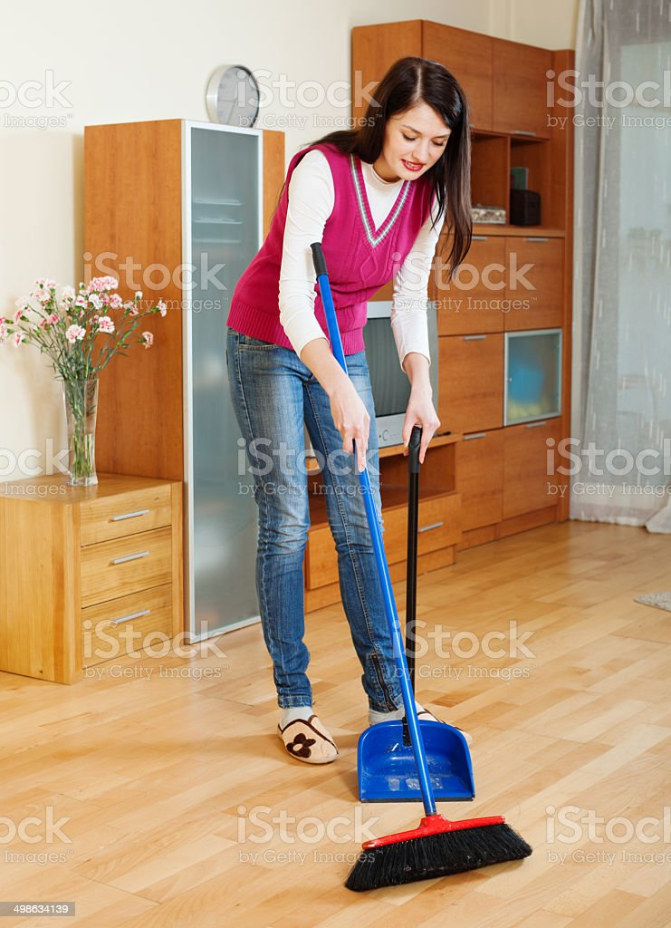Brunette  woman sweeping the floor stock photo