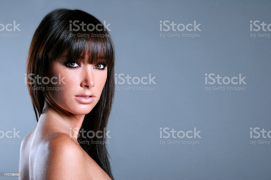Brunette woman with bangs on a gray background royalty-free stock photo