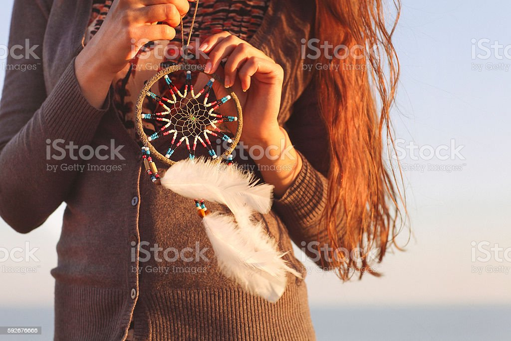 Brunette woman with long hair holding dream catcher stock photo