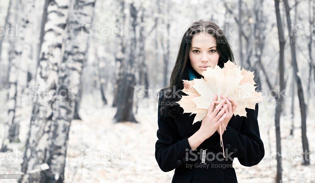 Brunette woman with maple leaves royalty-free stock photo