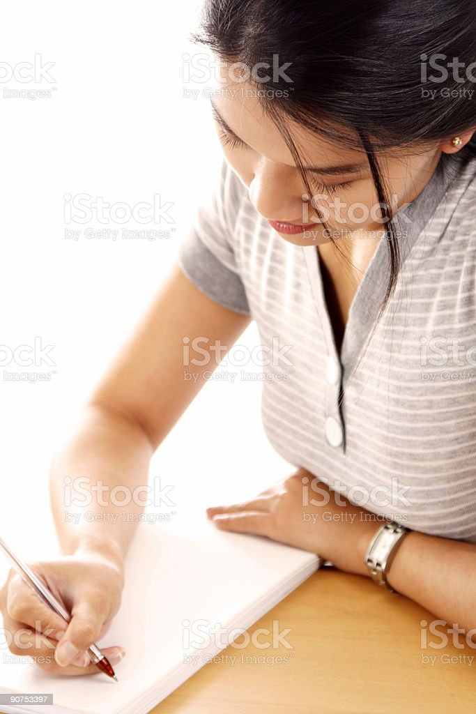 Brunette woman writing on paper stock photo