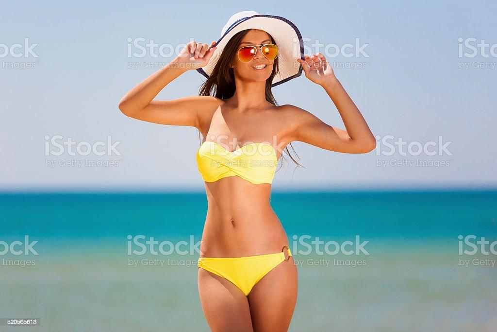 brunette woman yellow bikini sea stock photo