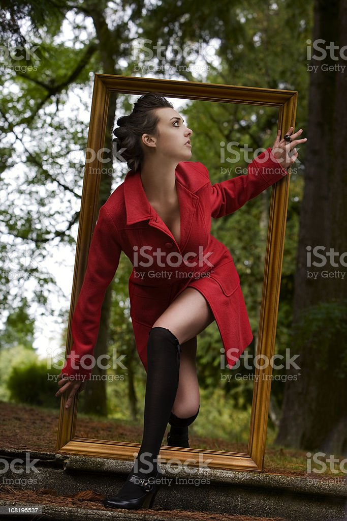 Brunette Young Woman in Forest Climbing Through Picture Frame royalty-free stock photo