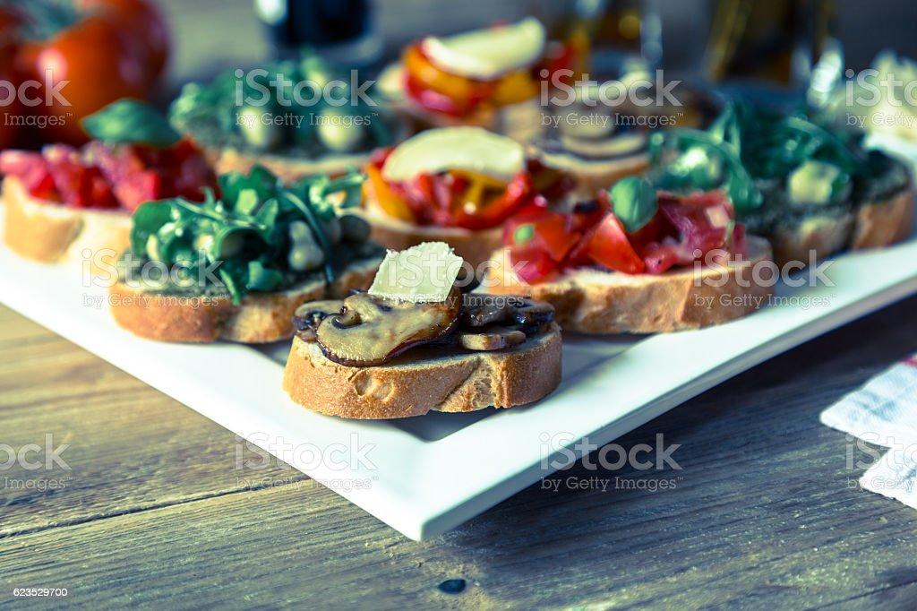 Bruschetta with beans and arugula, mushrooms, goat cheese stock photo