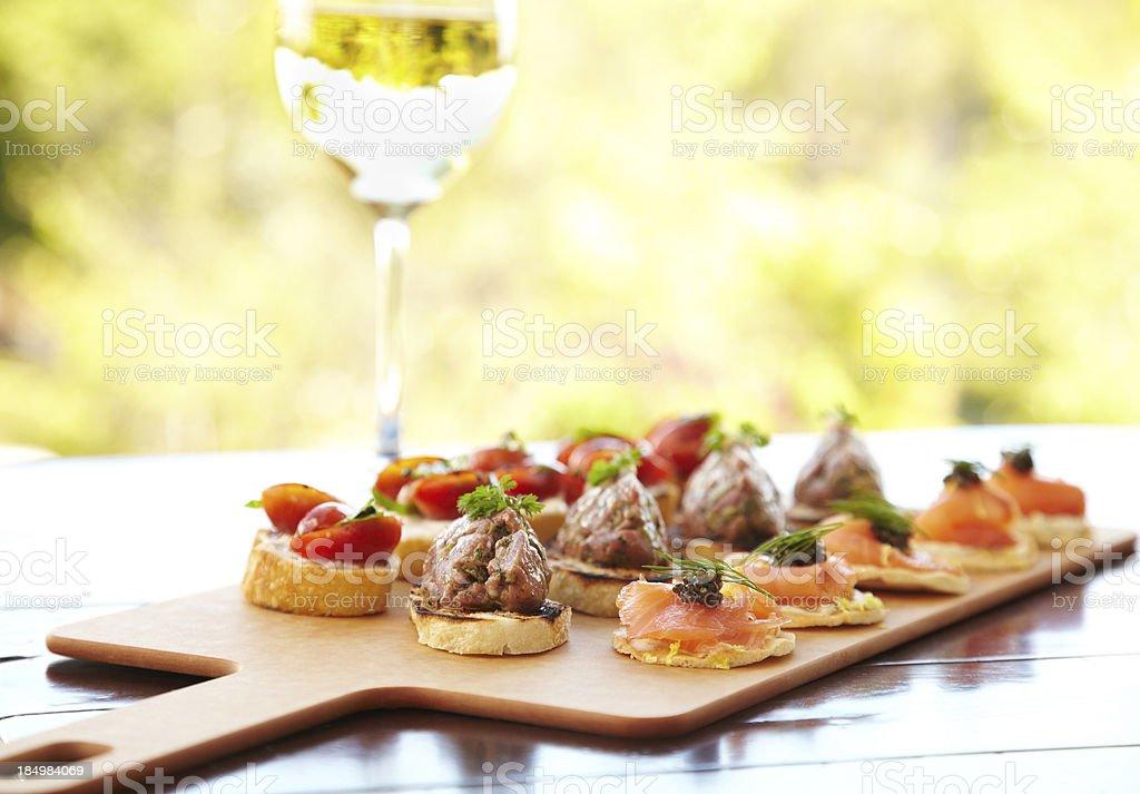 Bruschetta with cheese, tomatoes, foie gras, and wild salmon stock photo