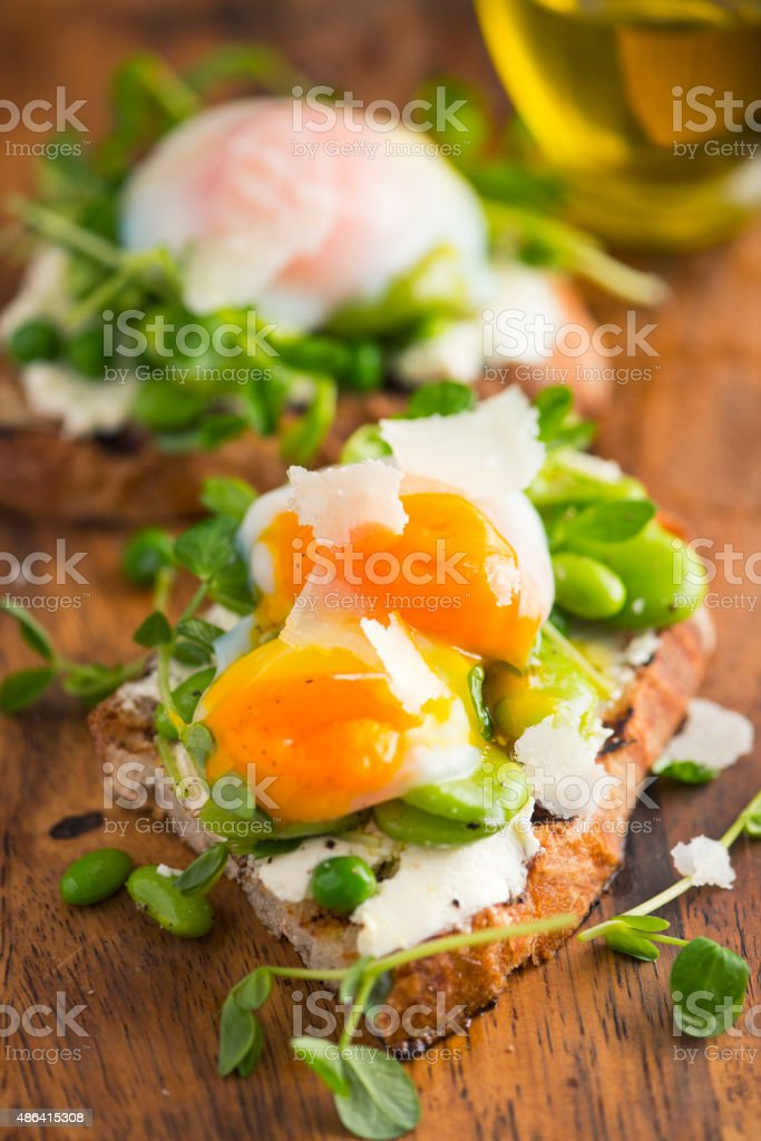 Bruschetta with Cream Cheese, Beans and Pea Sprout and Poached Egg stock photo