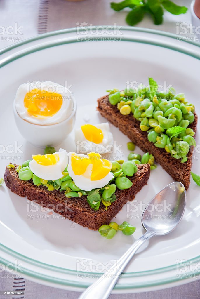 Bruschetta with green peas, mint and egg stock photo