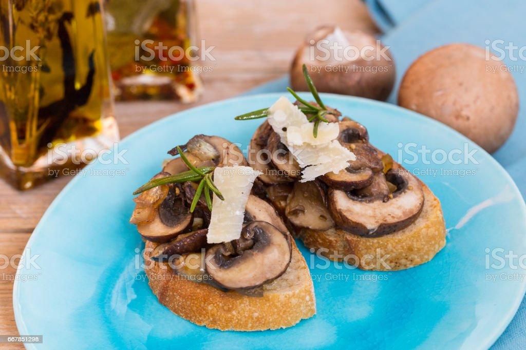 Bruschetta with mushrooms on a wooden board stock photo