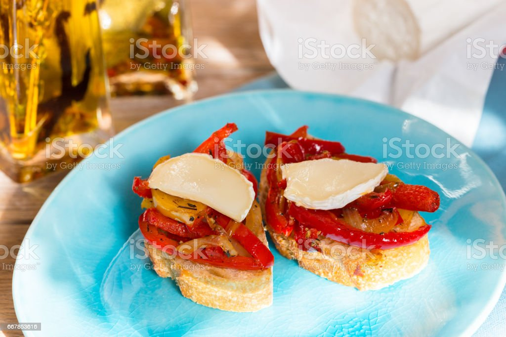 Bruschetta with peppers and goat cheese on a wooden board stock photo