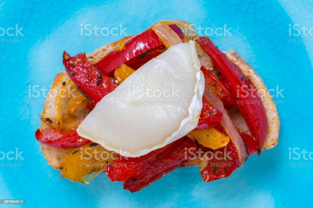 Bruschetta with peppers and goat's cheese on a turquoise plate stock photo