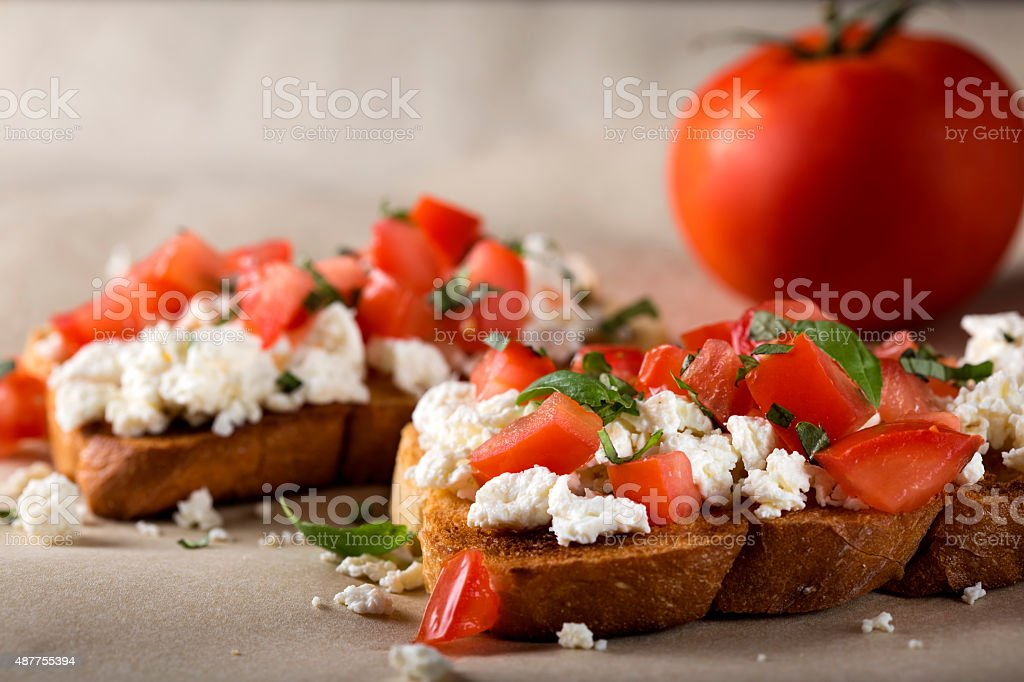 Bruschetta with roasted tomatoes, cheese and herbs stock photo