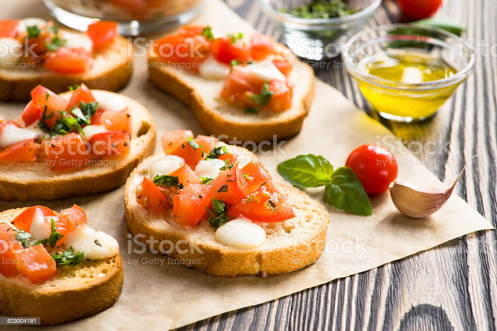 Bruschetta with roasted tomatoes, mozzarella cheese, garlic and stock photo