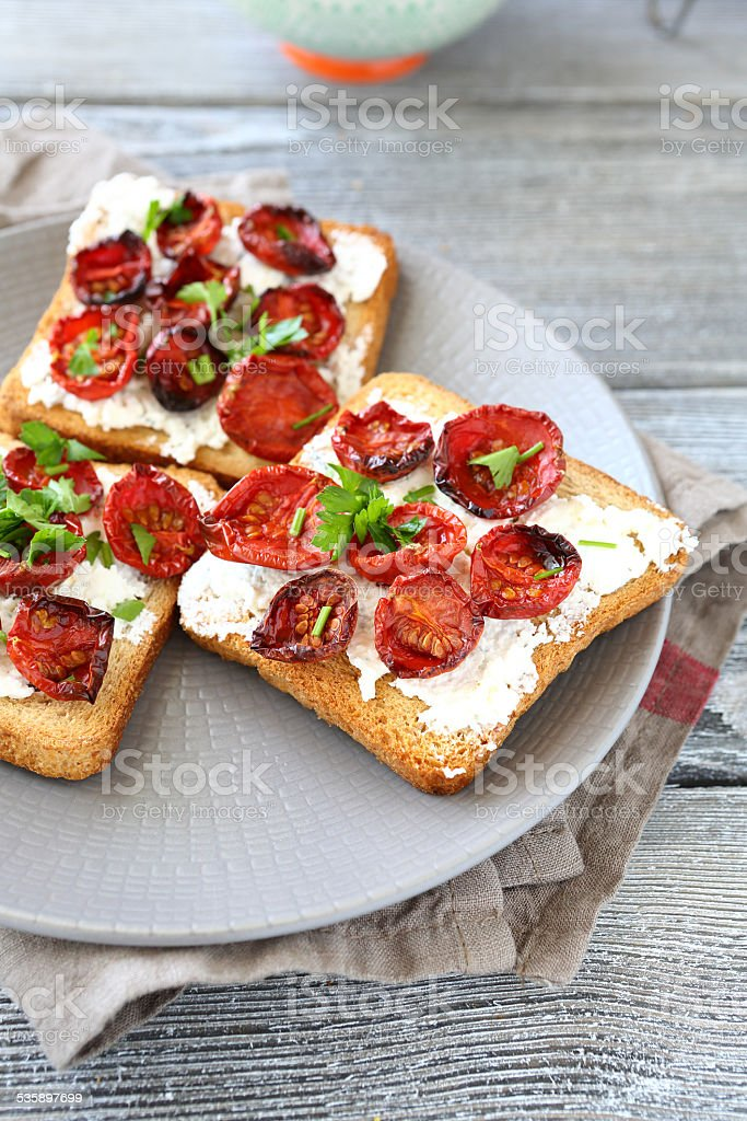 Bruschetta with sun-dried tomatoes and cheese on a plate stock photo