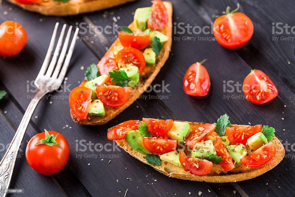 Bruschetta with tomato, avocado and herbs stock photo